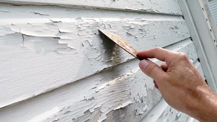 Showing exterior paint preparation, using a paint scraper remove peeling paint