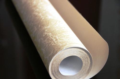 A light coloured roll of wallpaper on a dark backgroud